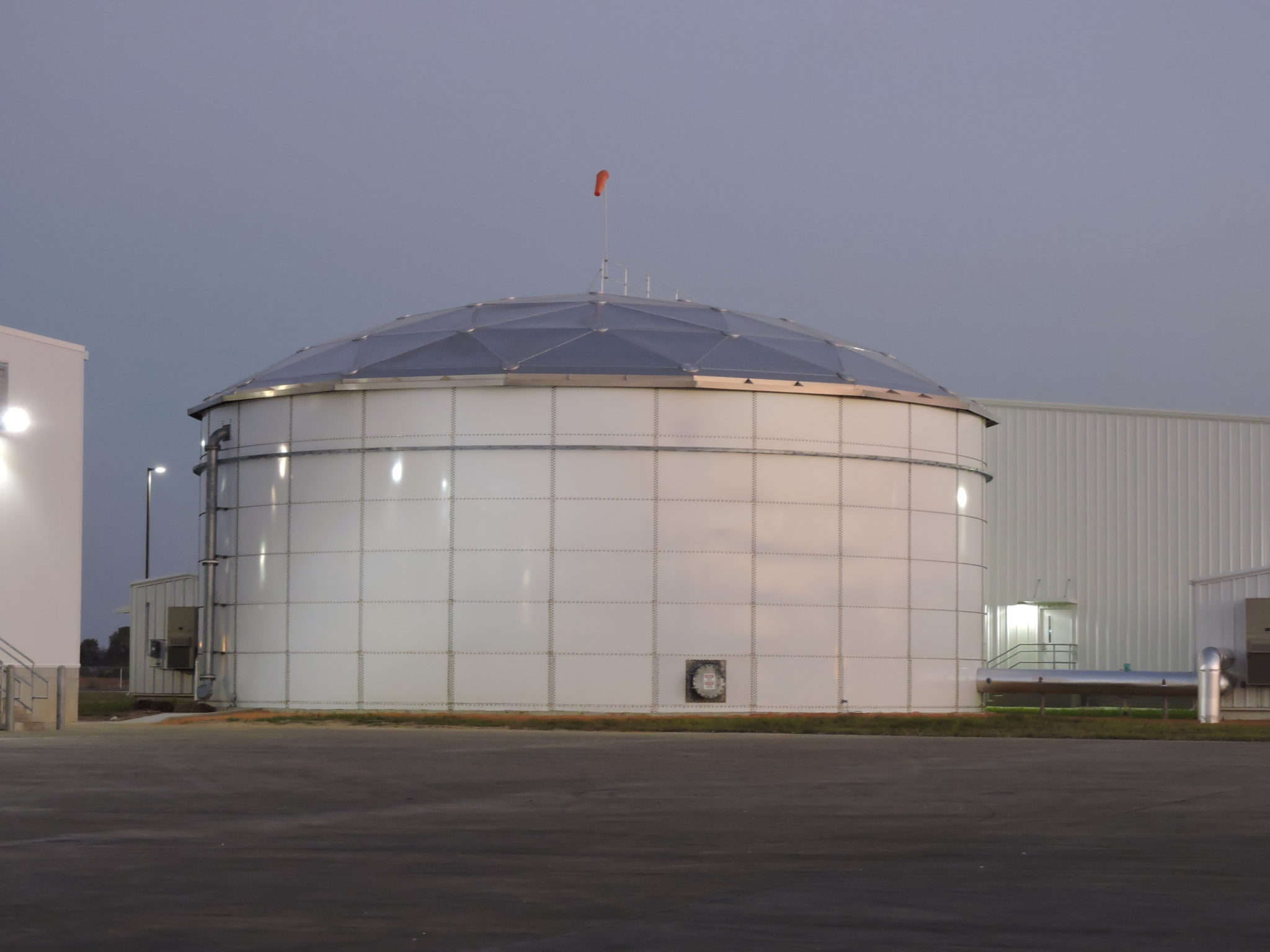 White bolted water storage tank with windsock