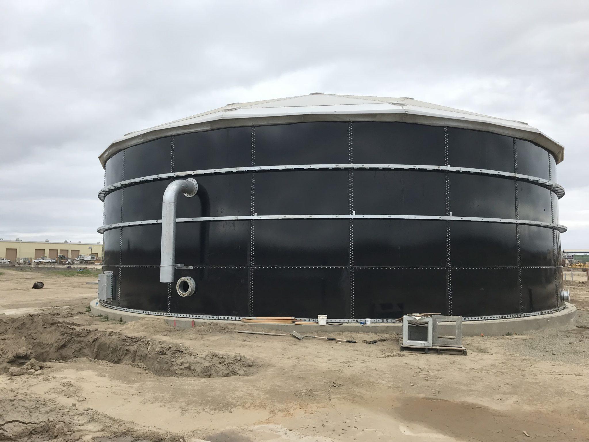 Dark blue bolted water storage tank in a dirt field