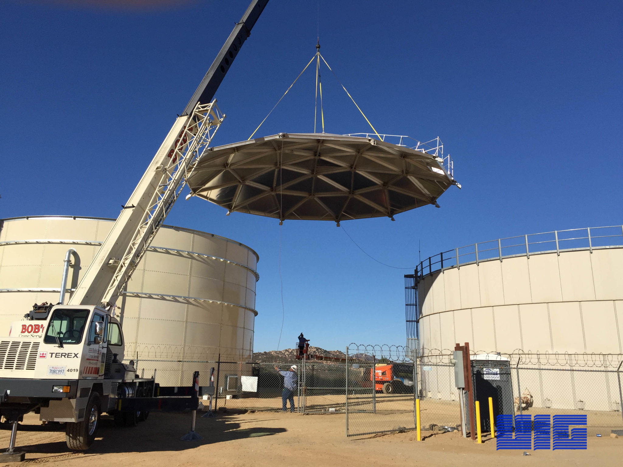 Crane lifting an aluminum dome roof on top of glass fused to steel bolted tank