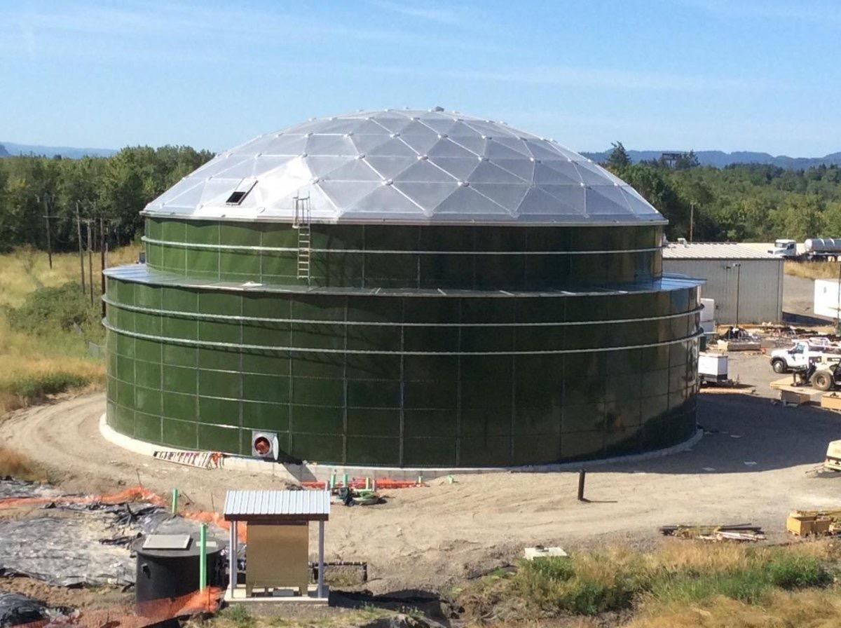 A green, double-walled bolted leachate tank with an aluminum dome roof