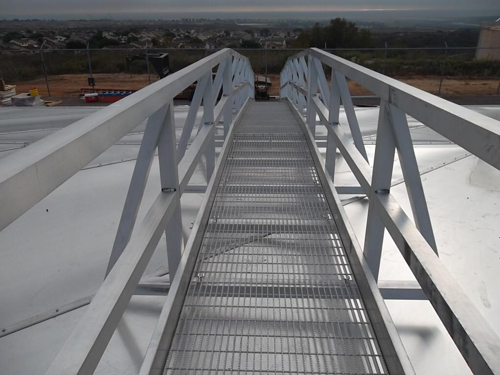 An aluminum walkway going across an aluminum reservoir cover