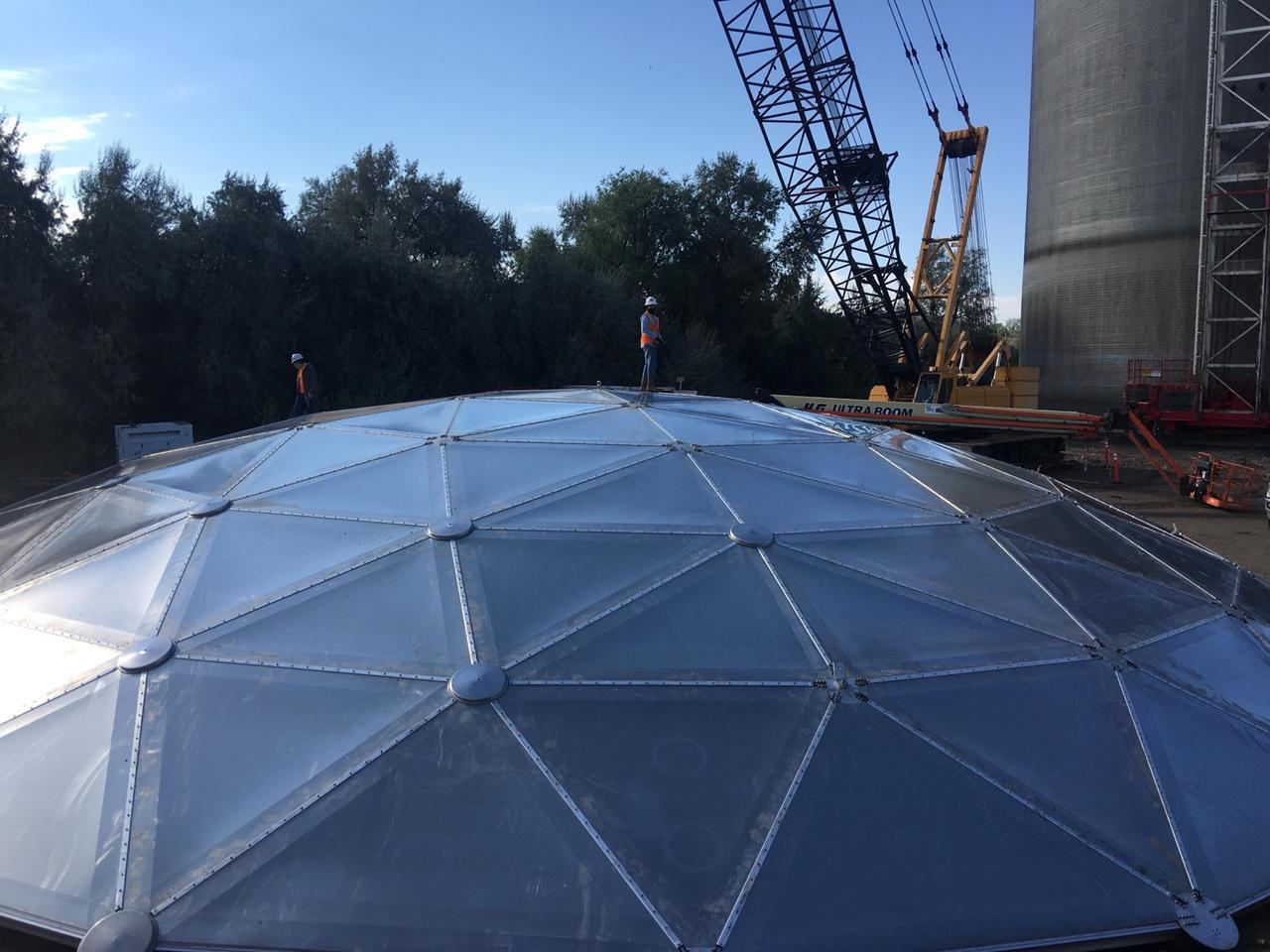 A construction worker standing on top of an aluminum geodesic dome roof.
