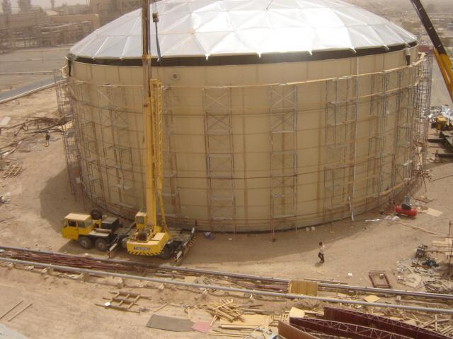 Cranes putting an aluminum dome on top of a tan epoxy bolted tank