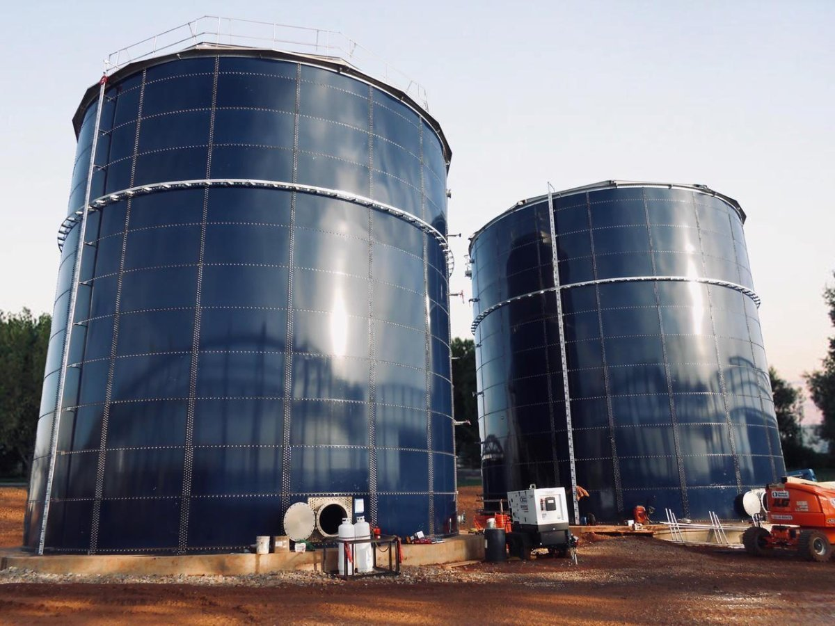 Two blue glass fused-to-steel storage tanks with open manways