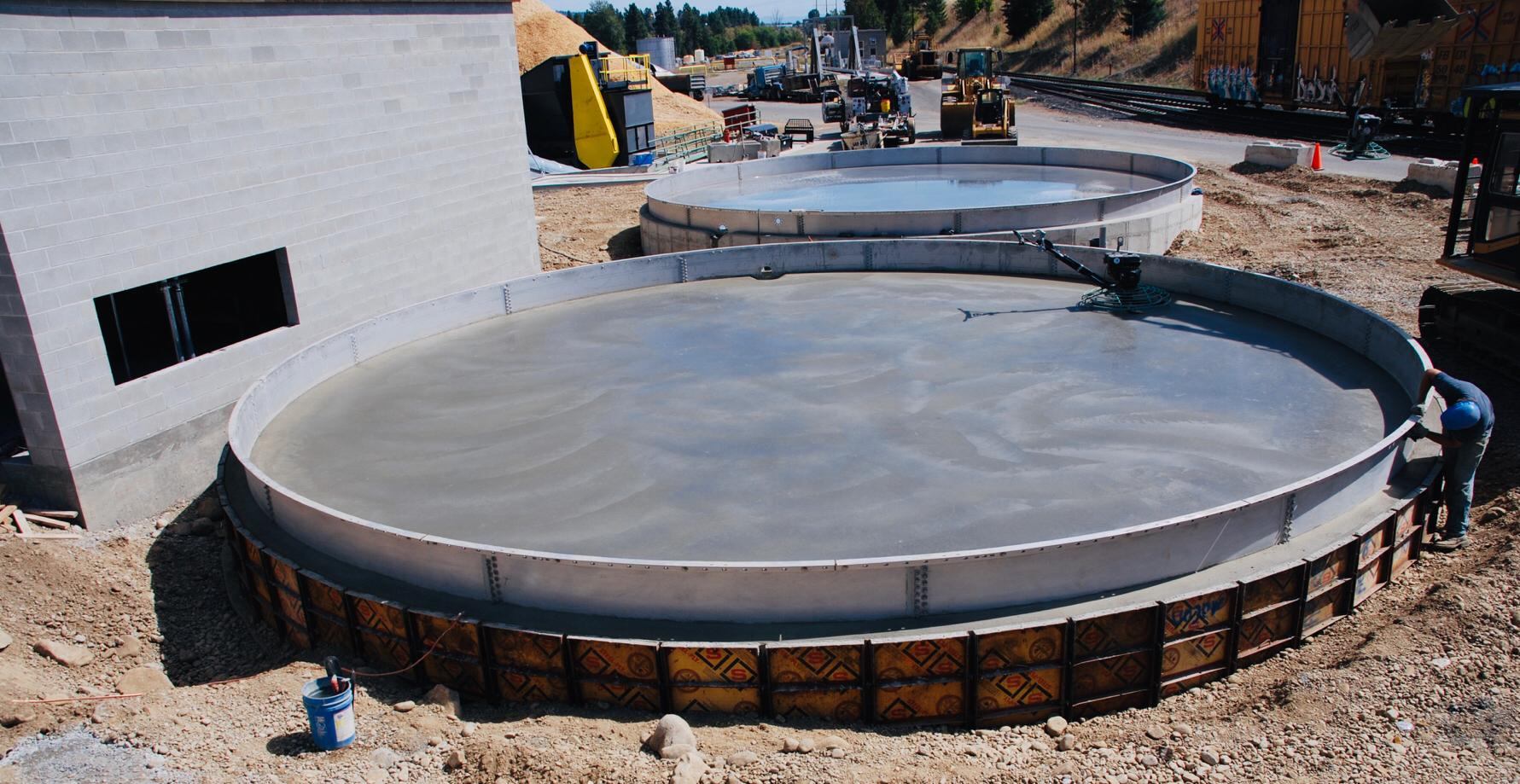 Worker installing the first ring of a bolted steel water tank, embedded in concrete
