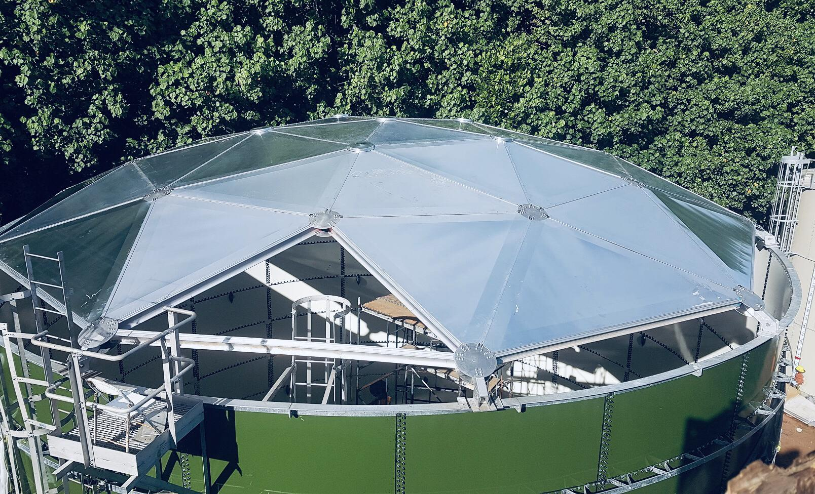 An aluminum geodesic dome roof being installed on a green glass fused to steel tank