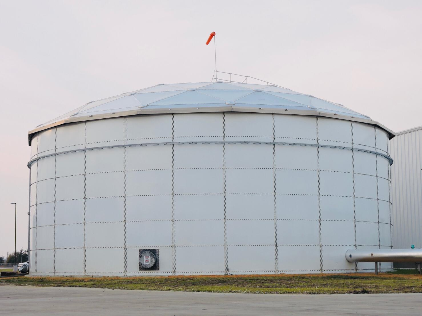 A white bolted tank with an aluminum dome and a red windsock on top