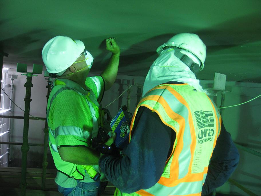 Two workers wearing masks inspecting the roof of a welded storage tank.