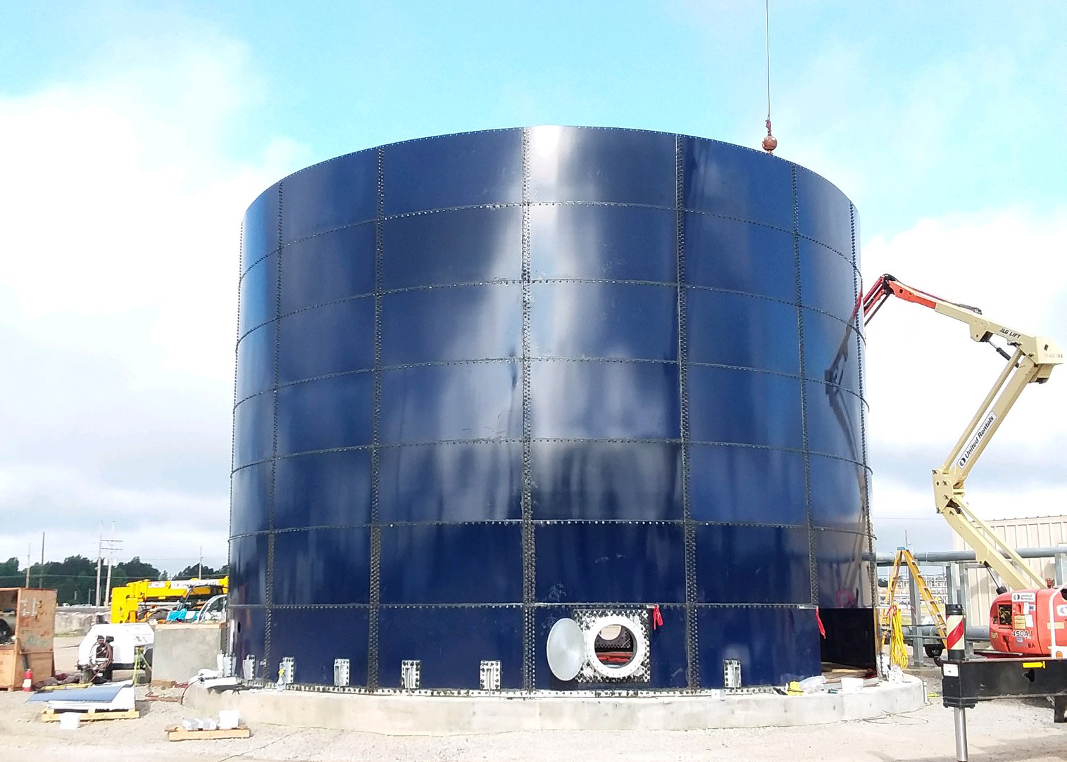 A crane installing of 7 rings on a blue glass fused-to-steel storage tank