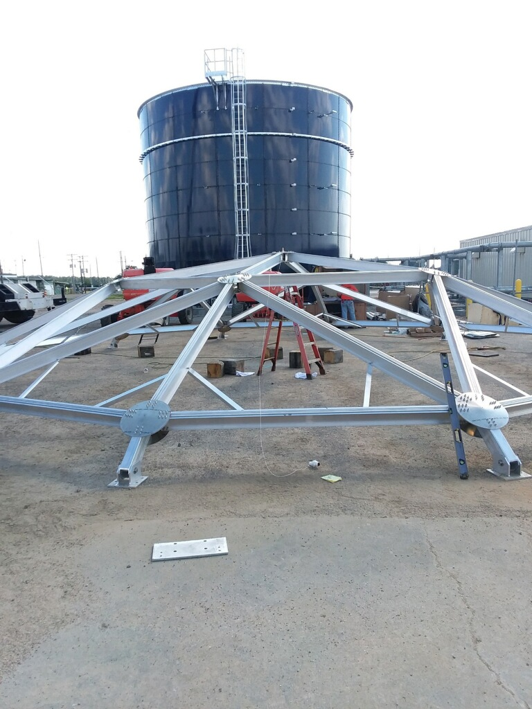 Frame for an aluminum geodesic dome with a blue water tank in the background