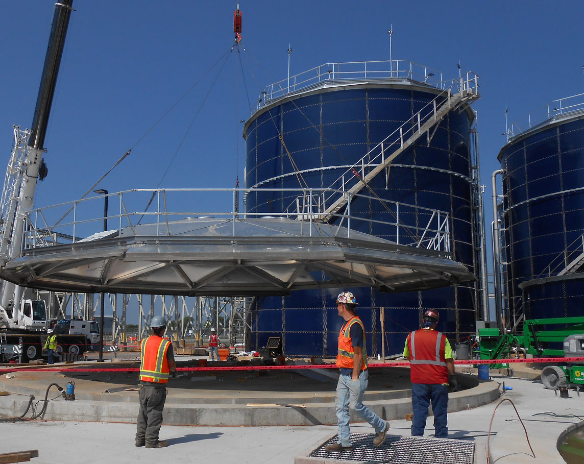 Workers lifting an aluminum geodesic dome for a bolted storage tank