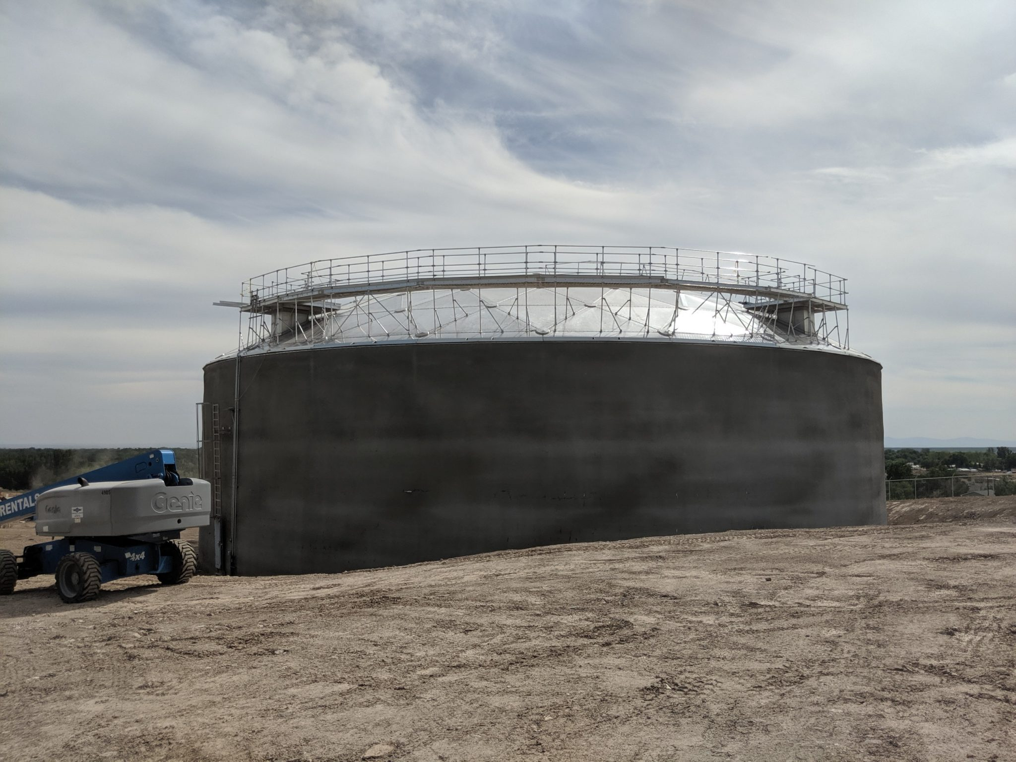 A partially buried concrete water storage tank with an aluminum geodesic dome with a catwalk
