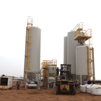 A Big Bag Concrete Processing Plant with five tanks and a forklift