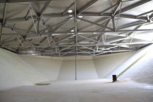 Inside of an empty water reservoir with aluminum roof above.