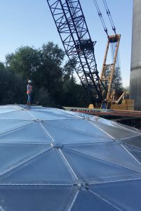 Worker in a mask on top of a large geodesic tank dome with boom lift in background