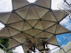 Underside of an aluminum geodesic dome in a star shape. Cloudy blue sky and safety cage.
