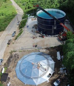 Water in a bolted steel tank and aluminum dome roof on the ground at a job site