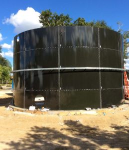 Dark green bolted water tank with exposed nozzles. Blue sky, dirt lot.