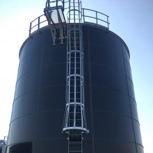Top portion of a water storage tank with ladder and standoff