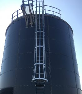 Galvanized steel safety ladder on the side of a bolted water tank