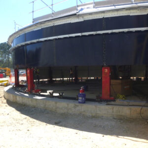 Red hydraulic jacks lifting steel water tank panels at a jobsite.