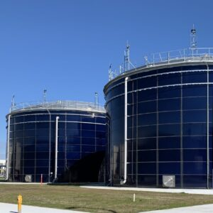 Two blue bolted water storage tanks with blue sky and grass