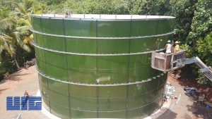 Green Glass Fused to Steel Tank in Pago Pago with installers in a bucket and forest behind.