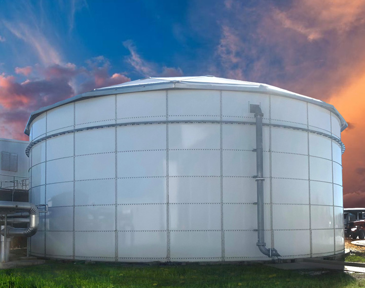 White paneled tank with an overflow pipe against a blue and orange sunset sky.