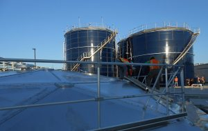 Two Blue Glass Fused to Steel Water Tanks with workers installing a hatch on an aluminum dome.