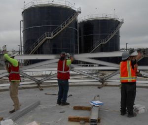 Installers erecting the beams for an aluminum dome tank roof. Two bolted tanks behind.