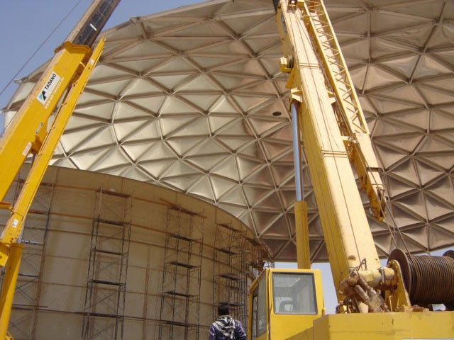 Large Aluminum Geodesic Dome being installed with a crane atop a bolted tank