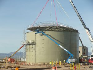 Using a crane and straps to install a geodesic dome roof on a large bolted tank