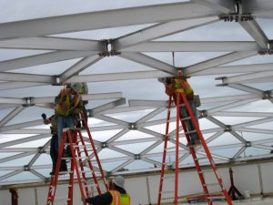 Five men installing beams for an aluminum dome roof
