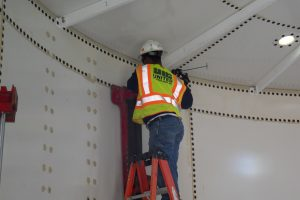 Worker on a ladder applying sealant to panels on a bolted tank