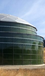 Green bolted tank panels and silver aluminum dome roof on a concrete pad with a dry field in foreground.