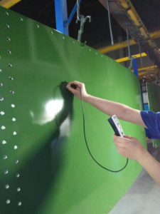 Worker testing the spray coating thickness on a glass lined tank panel