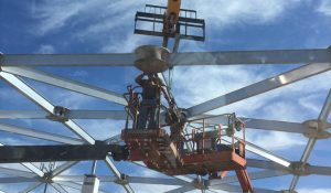Workers installing a round aluminum hub and beams from a boom lift. Blue sky with clouds behind/