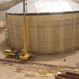 Large Bolted Water Tank with aluminum dome roof. Heavy equipment and dirt job site.