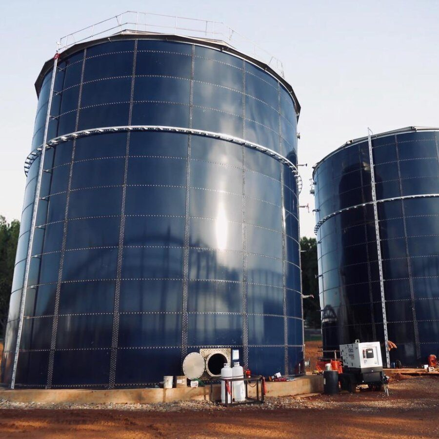 Two blue glass fused to steel bolted tanks. Dirt field and skip steer in forerground.
