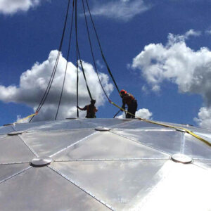 Installers on top of a geodesic dome roof