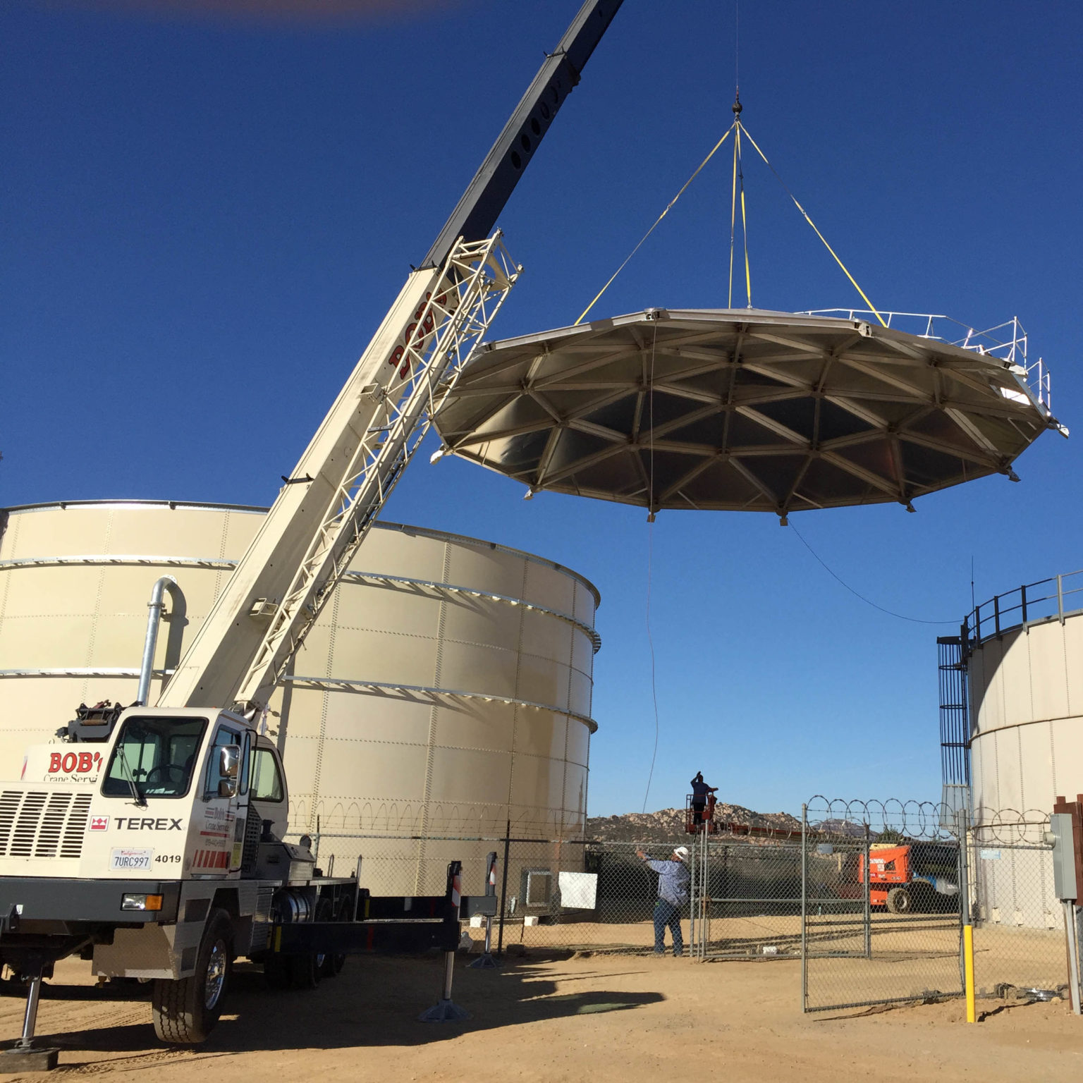 Lifting a geodesic dome atop an tan bolted water tank.