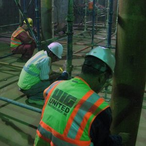 Three workers installing internal supports