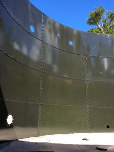 Inside olive green glass fused to steel tank with openings in the plates.