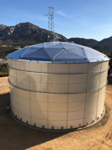 Tan Bolted Water Tank with Aluminum Dome on the side of a hill. Mountains and power tower in background.