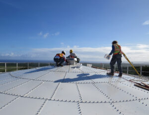 Installers on top of a glass fused to steel tank, installing a vent