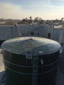 Looking at the top of a green water storage tank next to concrete buildings.