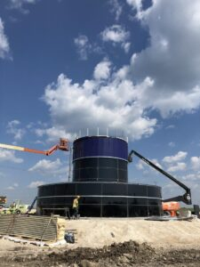 Blue double wall bolted tank on top of a sand hill. Installers using cranes to fit up the panels.