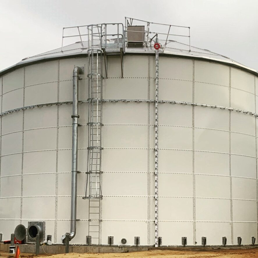 White panel tank with a level indicator, ladder with safety cage and overflow pipe.