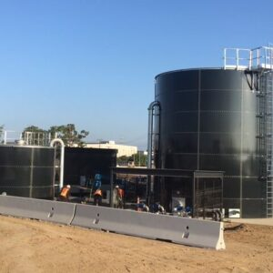 Men installing two dark gray paneled tanks with piping, ladders, cages.