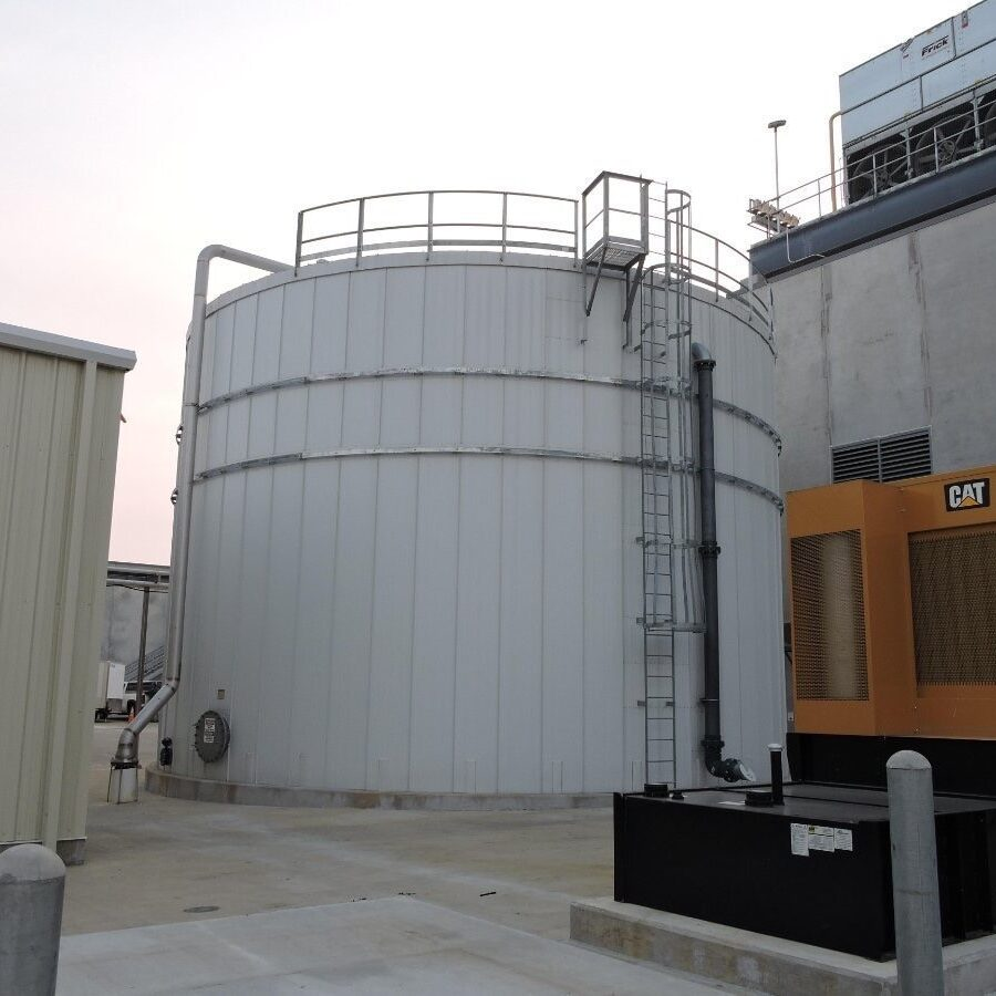 White water storage tank with ladder and pipe next to a building.